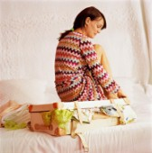 JB188 11 Young woman sitting on an over packed suitcase on a bed What to Pack